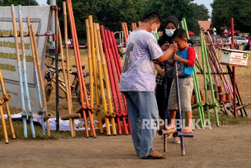 Anak-anak bermain permainan tradisional egrang di Alun-alun Selatan, Yogyakarta, Senin (14/6). Permainan tradisional seperti egrang menarik untuk anak-anak. Dengan bayar seikhlasnya anak-anak bisa bermain egrang dengan berbagai ukuran di sini. Setiap sore lapak Raja Egrang sudah ada untuk melayani warga.
