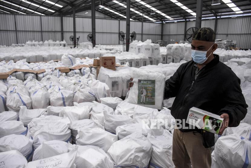 Petugas menyiapkan logistik protokol kesehatan di Gudang KPU Kabupaten Bandung, Kampung Sawah, Soreang, Kabupaten Bandung, Kamis (3/12). Komisi Pemilihan Umum (KPU) Kabupaten Bandung menyiapkan logistik protokol kesehatan seperti pakaian hazmat, masker, sarung tangan, sabun, tempat cuci tangan dan pelindung wajah yang kemudian akan di distribusikan ke 6.874 TPS guna meminimalisir penyebaran Covid-19 saat pelaksanaan Pilkada Kabupaten Bandung 2020 pada Desember mendatang. Foto: Abdan Syakura/Republika