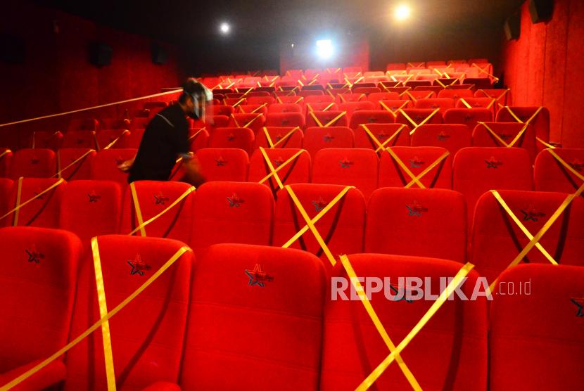 Petugas memasang pita jaga jarak tempat duduk di dalam studio saat pembukaan kembali bioskop. Ilustrasi.