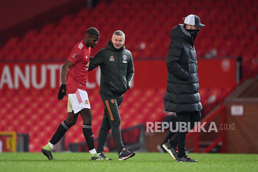 Manajer Manchester United Ole Gunnar Solskjaer (tengah) dan Paul Pogba (kiri).