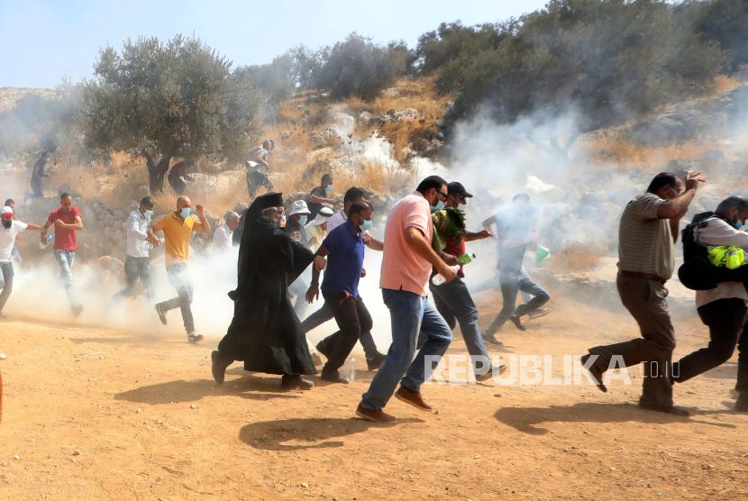Warga Palestina lari untuk mencari perlindungan dari gas air mata yang ditembakkan oleh tentara Israel selama demonstrasi menentang permukiman Israel di desa Bet Dajan dekat kota Nablus, Tepi Barat utara, Jumat (9/10/2020).