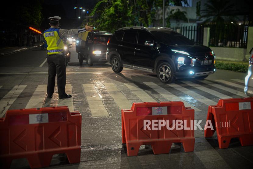 Petugas kepolisian mengatur lalu lintas saat penutupan akses jalan selama PPKM Darurat.