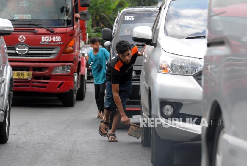 Warga mengganjal ban mobil pemudik di kawasan Nagreg, Kabupaten Bandung, Jawa Barat, Rabu (13/6).