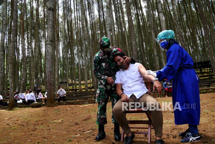 Tenaga kesehatan menyuntin vaksin Sinovac untuk pelaku wisata di kawasan wisata Hutan Pinus Mangunan, Bantul Yogyakarta, Rabu (28/7). Sebanyak dua ribu pelaku wisata menjadi target vaksinasi massal Covid-19 oleh Pemerintah Kabupaten Bantul. Pada vaksinasi massal kali ini menggunakan vaksin Sinovac.