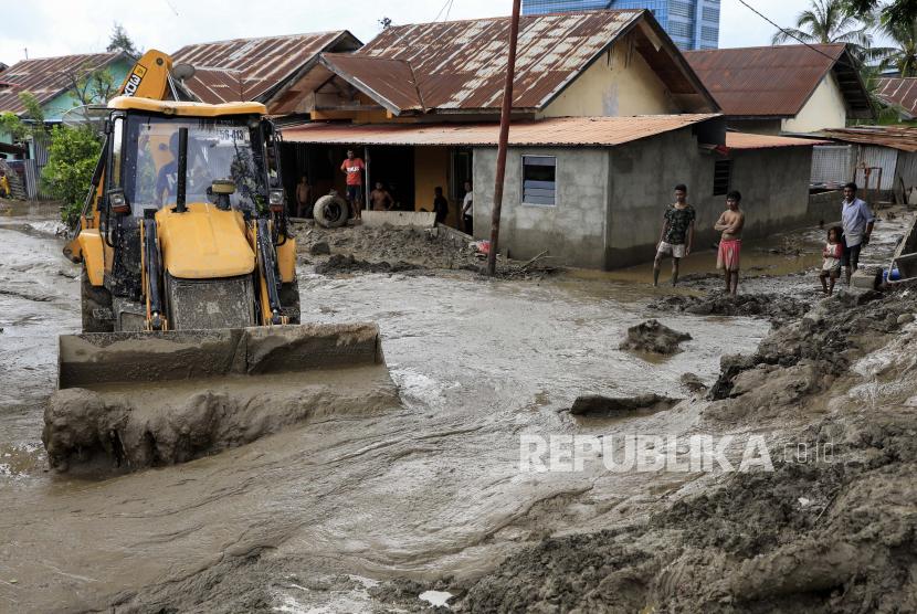 Sebuah ekskavator beraksi membersihkan lumpur dari jalan pasca banjir di Dili, Timor Leste, juga dikenal sebagai Timor Leste, 05 April 2021. Puluhan orang tewas dan puluhan hilang karena banjir dan tanah longsor akibat hujan lebat melanda bagian timur Indonesia dan Timor Leste selama akhir pekan.