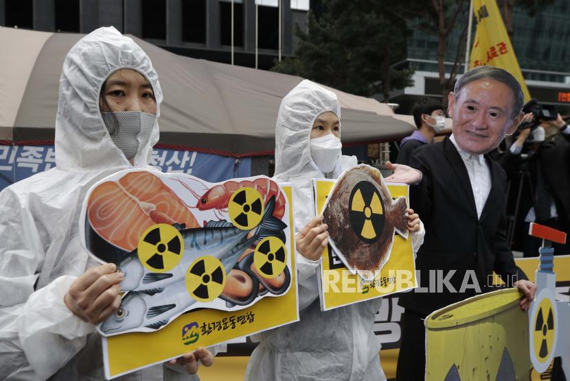 Aktivis lingkungan yang mengenakan topeng Perdana Menteri Jepang Yoshihide Suga dan pakaian pelindung tampil untuk mengecam keputusan pemerintah Jepang tentang air Fukushima, dekat kedutaan Jepang di Seoul, Korea Selatan, Selasa, 13 April 2021.