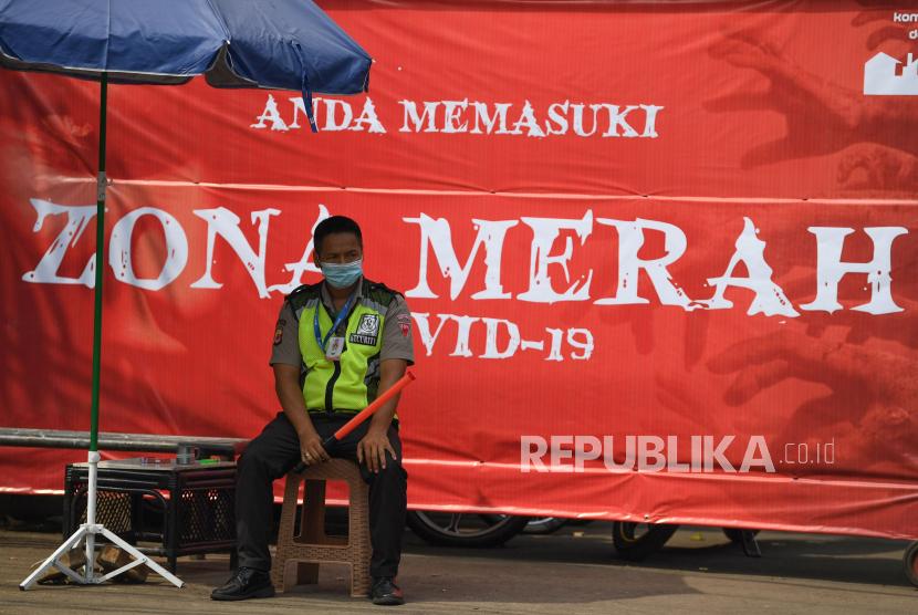 Seorang petugas keamanan berjaga dengan latar belakang spanduk pemberitahuan lokasi zona merah COVID-19 di Depok, Jawa Barat. (ilustrasi)