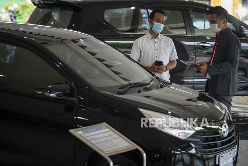 Karyawan menjelaskan salah satu produk mobil kepada calon pembeli di salah satu dealer di Jakarta, Senin (15/2/2021). Pemerintah memberikan keringanan pajak penjualan atas barang mewah (PPnBM) mobil baru ketegori 4x2 atau sedan dengan mesin sampai dengan 1.500 cc mulai Maret 2021 dengan tiga tahap untuk meningkatkan pertumbuhan industri otomotif dengan