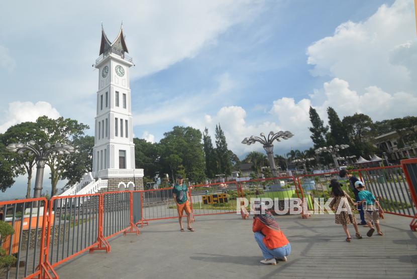 Pengunjung berfoto di pelataran Jam Gadang yang ditutup dengan pagar, di Bukittinggi, Sumatera Barat. Satgas COVID-19 Kota Bukittinggi, Sumatera Barat, memaksa 162 pelanggar protokol kesehatan (prokes) yang terjaring operasi yustisi di daerah ini menjalani tes usap.