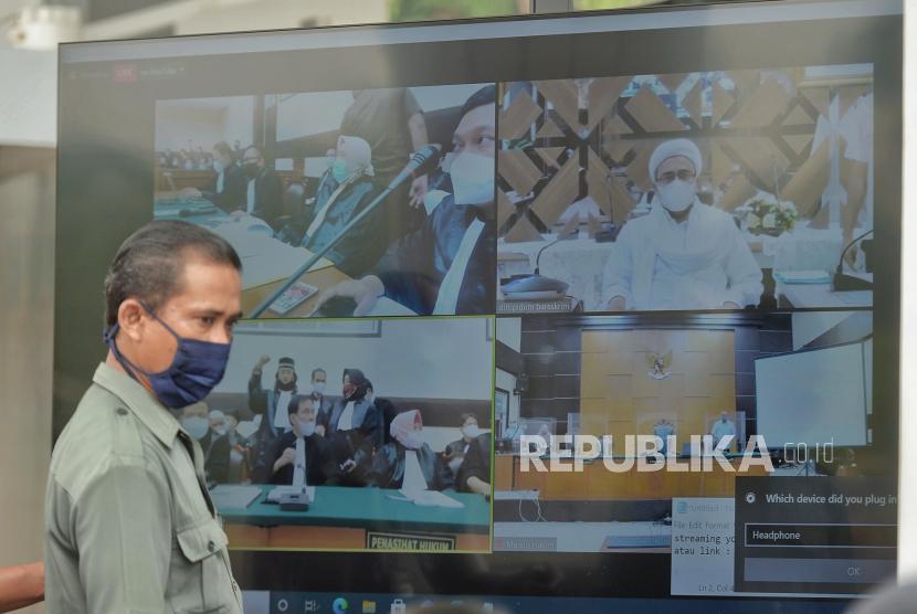 Layar yang menampilkan suasana sidang perdana atas kasus pelanggaran protokol kesehatan dengan terdakwa mantan Pemimpin Front Pembela Islam Rizieq Shihab yang digelar secara virtual di Pengadilan Negeri Jakarta Timur, Selasa (16/3). Ketua Majelis Hakim Pengadilan Negeri Jakarta Timur Suparman Nyompa memutuskan menunda sidang dakwaan akibat terkendala teknis, dan akan dilanjutkan pada Jumat 19 Maret 2021 mendatang. Republika/Thoudy Badai