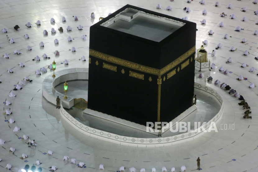 Muslim pilgrims pray around the Kaaba, the cubic building at the Grand Mosque, as they keep social distancing during the minor pilgrimage, known as Umrah, marking the holy month of Ramadan, in the Muslim holy city of Mecca, Saudi Arabia, Monday, April 12, 2021. During Ramadan, the holiest month in Islamic calendar, Muslims refrain from eating, drinking, smoking and sex from dawn to dusk.
