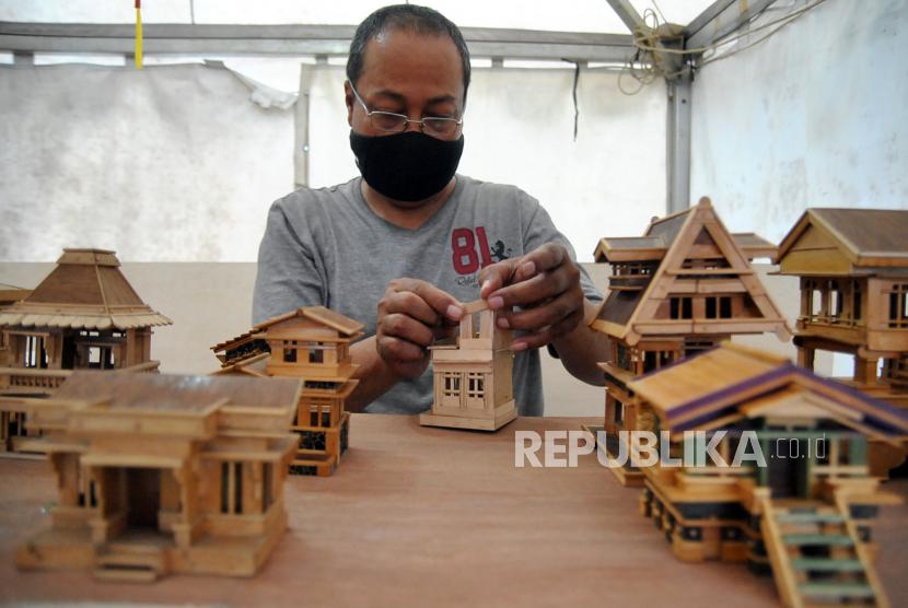 Perajin mengerjakan pembuatan kerajinan miniatur rumah dari bahan stik es krim saat Pesta Rakyat di Kota Bogor, Jawa Barat, Senin (8/2/2021). Menteri Keuangan Sri Mulyani Indrawati akan menyalurkan Banpres Produktif Usaha Mikro (BPUM) sebesar Rp3,6 triliun kepada tiga juta penerima mulai Juli-September 2021.