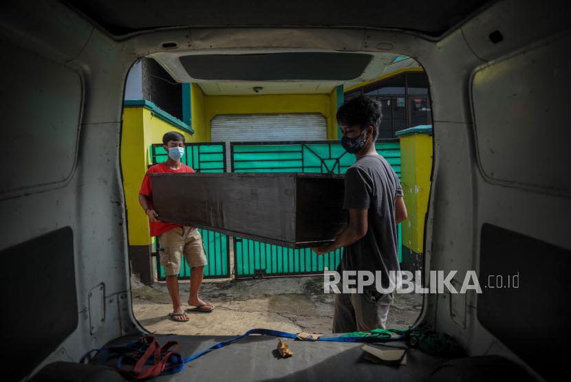 Perajin membawa pesanan peti jenazah untuk dikirim di Desa Cibeusi, Jatinangor, Kabupaten Sumedang, Jawa Barat, Jumat (25/6/2021). Perajin menyatakan sejak awal Juni 2021 permintaan peti jenazah seharga Rp1 juta per peti yang didistribusikan ke berbagai rumah sakit rujukan COVID-19 di Kota Bandung tersebut mengalami peningkatan hingga 80 persen atau 12 peti per hari dibandingkan bulan sebelumnya yang hanya empat peti jenazah per hari.