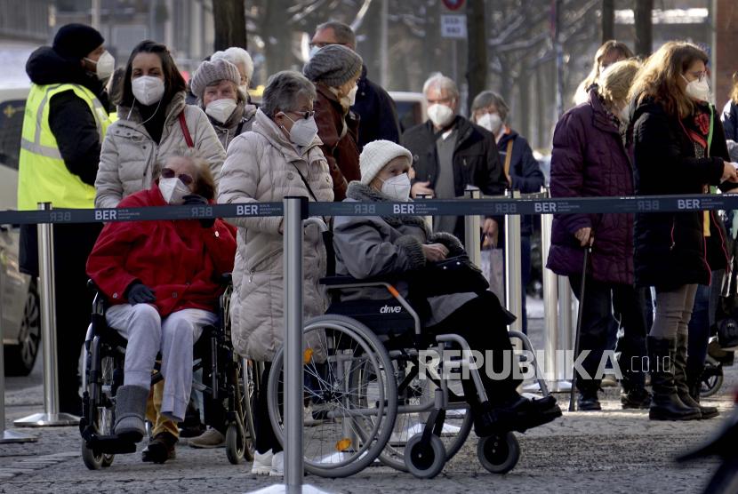 Orang-orang mengantre di depan pusat vaksinasi penyakit COVID -19 di