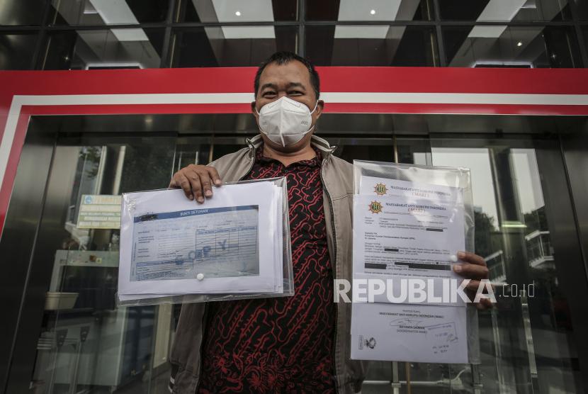 Koordinator Masyarakat Anti Korupsi Indonesia (MAKI) Boyamin Saiman menunjukkan sejumlah berkas usai menyampaikan pelaporan di gedung KPK, Jakarta.