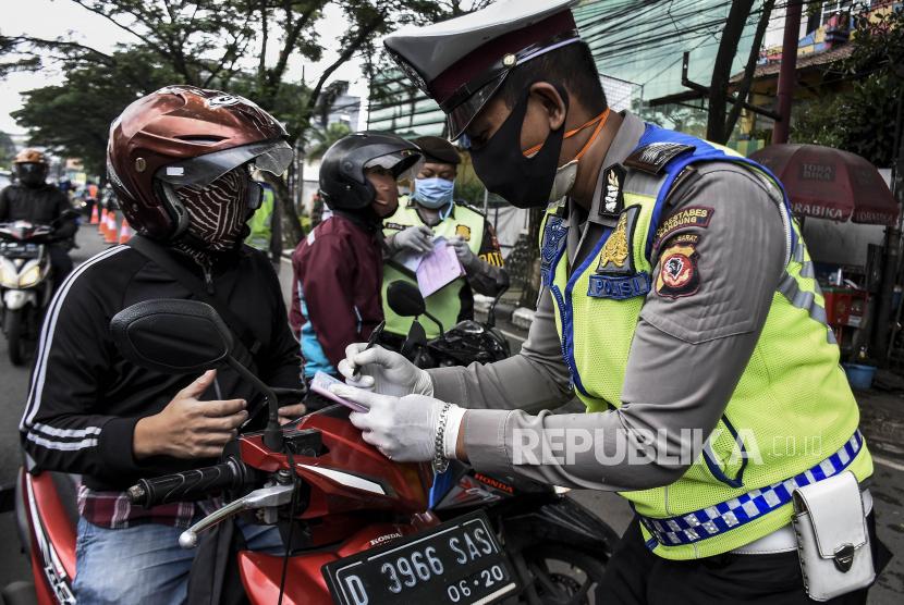 Petugas kepolisian memberikan surat teguran kepada pengendara yang melanggar saat penerapan Pembatasan Sosial Berskala Besar (PSBB) - ilustrasi