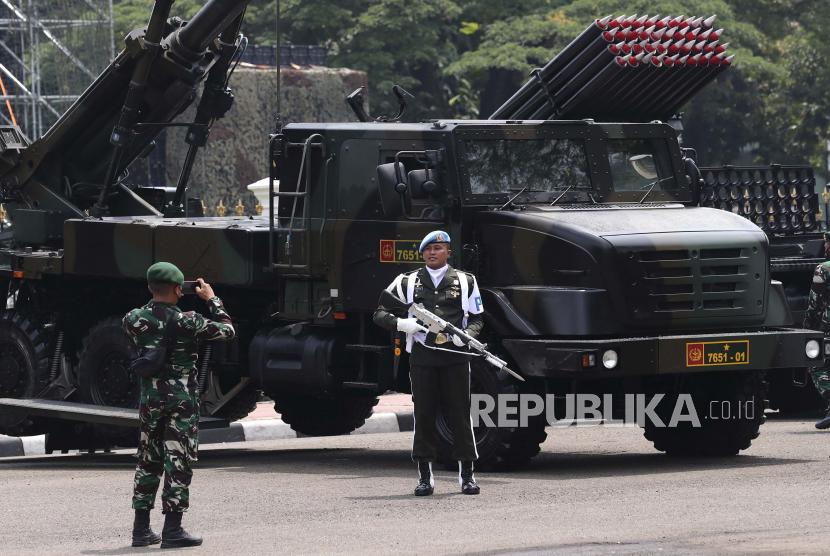 Seorang anggota pengawal presiden berfoto di dekat kendaraan militer yang dipajang di dekat Istana Kepresidenan selama perayaan HUT ke-76 Angkatan Bersenjata Republik Indonesia, di Jakarta, Indonesia, Selasa, 5 Oktober 2021.