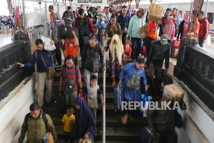 Penumpang kereta api Jayabaru  menuruni tangga pintu keluar di stasiun Kereta api Senen Jakarta, Kamis (21/2).