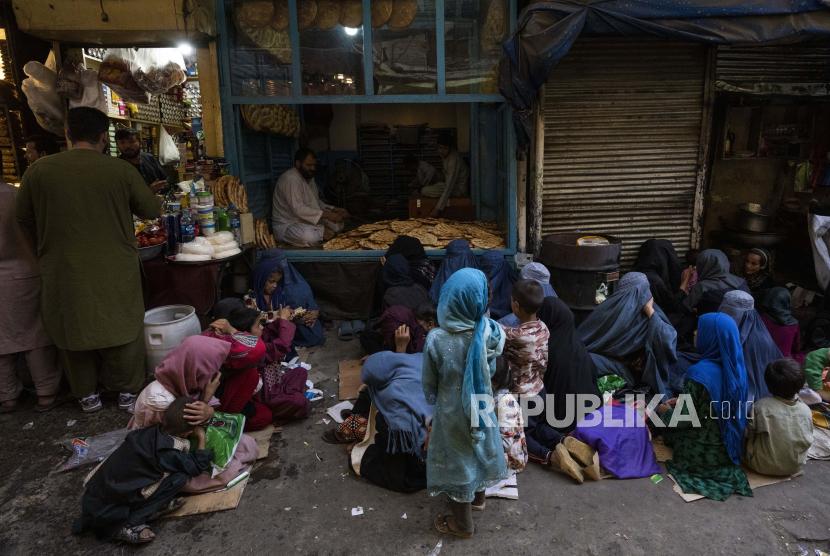 Wanita dan anak-anak Afghanistan duduk di depan toko roti menunggu sumbangan roti di Kota Tua Kabul, Afghanistan, Kamis, 16 September 2021.
