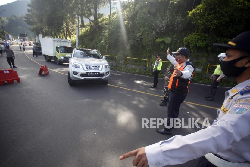 Petugas gabungan memutar balik kendaraan di titik pemeriksaan perbatasan Bogor-Cianjur, Jalan Raya Puncak, Kabupaten Bogor, Jawa Barat, Senin (1/6/2020). Petugas gabungan memperketat akses keluar masuk kendaraan yang melewati perbatasan dalam pemberlakuan Pembatasan Sosial Berskala Besar (PSBB) di Bogor