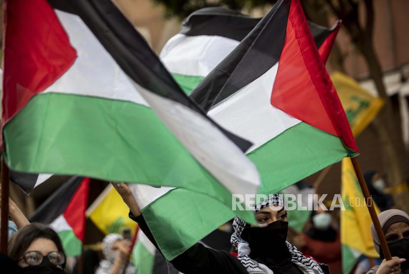 Warga Lebanon dan Palestina meneriakkan slogan dan mengibarkan bendera, selama unjuk rasa yang diselenggarakan oleh kelompok militan Hizbullah Lebanon untuk mengekspresikan solidaritas dengan rakyat Palestina, di pinggiran selatan Beirut, Lebanon, Senin, 17 Mei 2021.