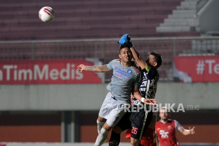 Kiper Persija Andritany menepis bola tandukan penyerang Persib Wander Luiz saat pertandingan Final Pertama Piala Menpora 2021 di Stadion Maguwoharjo, Sleman, Yogyakarta, Kamis (22/4). Pada babak pertama Persib tertinggal 0-2 dari Persija. Gol dicetak oleh Braif Fatari dan Tufik Hidayat.