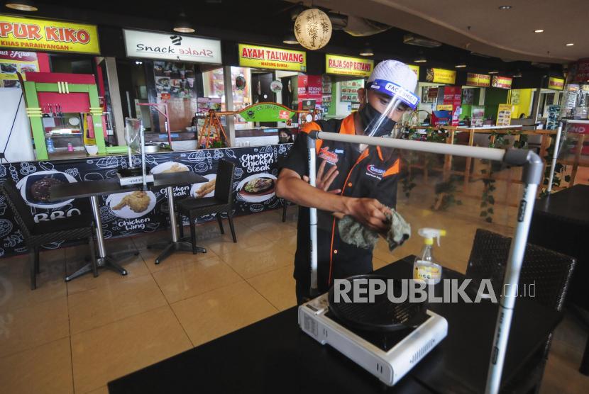 Pekerja membersihkan pembatas plastik di salah satu restoran di Bekasi, Jawa Barat, Ahad (7/6). Pembatas plastik itu dipasang untuk menjaga pembatasan jarak fisik antar pengunjung yang merupakan bagian dari penerapan protokol kesehatan di era new normal