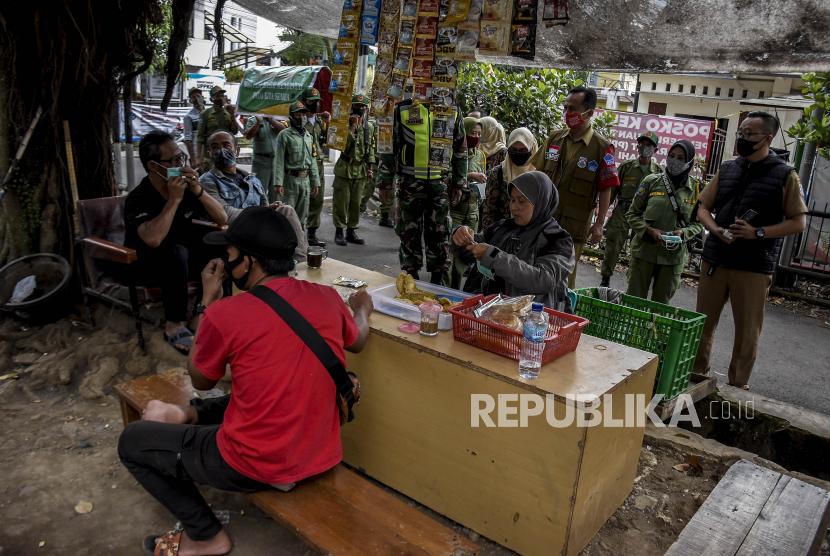 Petugas gabungan membagikan masker saat sosialisasi perpanjangan Pemberlakuan Pembatasan Kegiatan Masyarakat (PPKM) Skala Mikro.