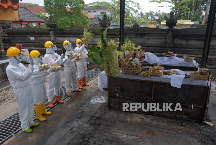 Petugas menggunakan pakaian hazmat dan alat pelindung diri saat melakukan proses kremasi jenazah pasien COVID-19 di Krematorium Sagraha Mandra Kantha Santhi, Desa Bebalang, Bangli, Bali, Sabtu (10/10/2020). Sejak bulan Mei hingga Oktober 2020 jenazah pasien COVID-19 di seluruh Bali sebagian besar dikremasi di krematorium tersebut sehingga tidak memerlukan lahan pemakaman.