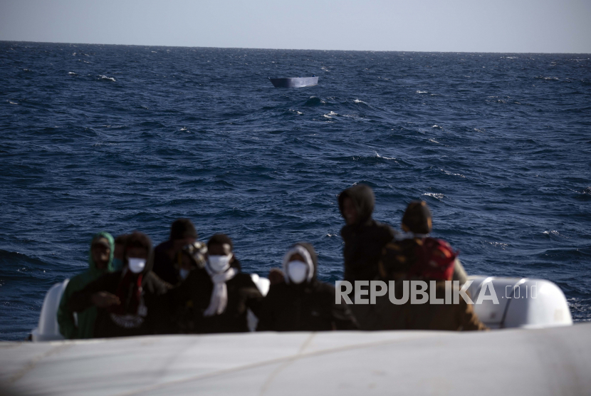 Para migran, kebanyakan dari mereka dari Eritrea, dibantu oleh pekerja bantuan dari LSM Spanyol Open Arms, setelah melarikan diri dari Libya dengan kapal kayu berbahaya di laut Mediterania, sekitar 110 mil utara Libya, pada Sabtu, 2 Januari 2021.