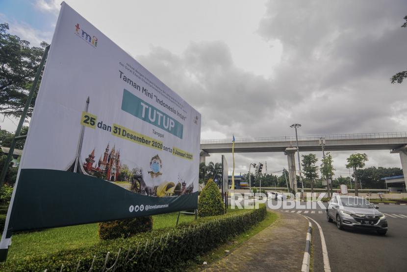 [Ilustrasi] Sebuah mobil melintas di dekat spanduk informasi yang memberitahukan penutupan Taman Mini Indonesia Indah (TMII).