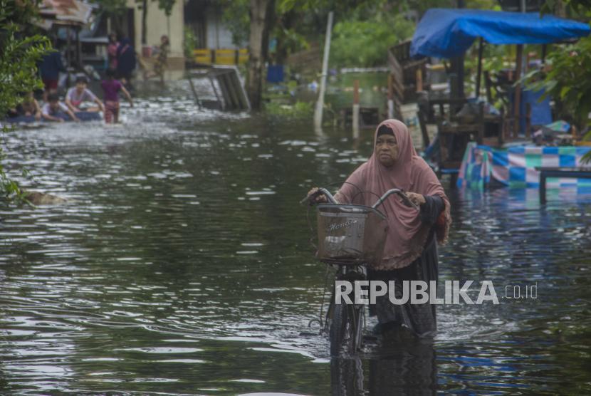 Warga menuntun sepedanya melintasi banjir yang merendam Jalan Prona di Banjarmasin, Kalimantan Selatan, Kamis (14/1/2021). Berdasarkan data yang telah dihimpun Badan Penanggulangan Bencana Daerah (BPBD) Provinsi Kalimantan Selatan dari tanggal 1 hingga 14 Januri, sebanyak 19.452 rumah terendam banjir di sejumlah wilayah di Kalimantan Selatan.
