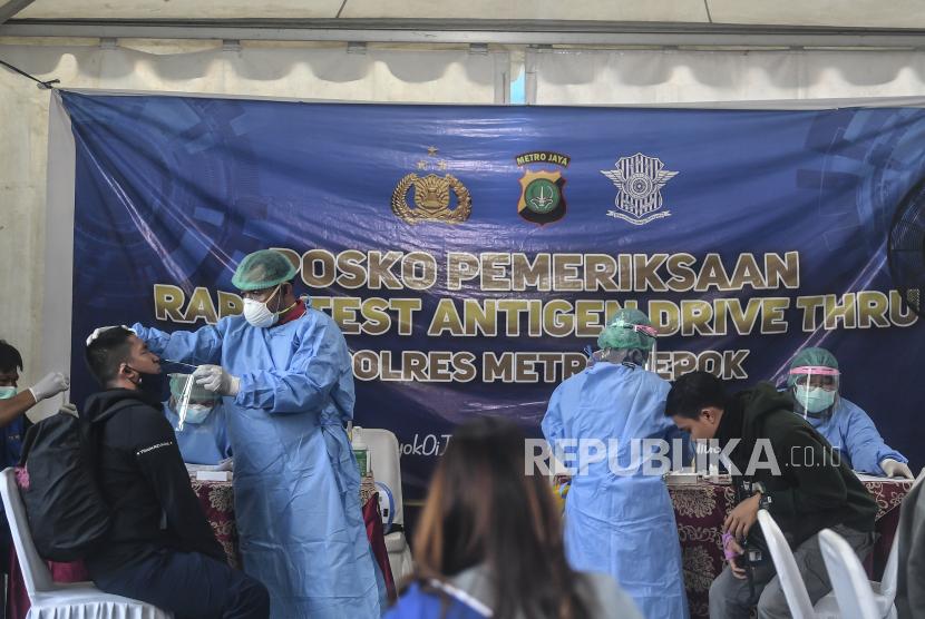 Petugas kesehatan melakukan swab antigen kepada warga bermotor di Depok, Jawa Barat, Selasa (25/5/2021). Swab antigen yang dilakukan Polres Metro Depok tersebut guna mencegah lonjakan kasus COVID-19 usai libur panjang.