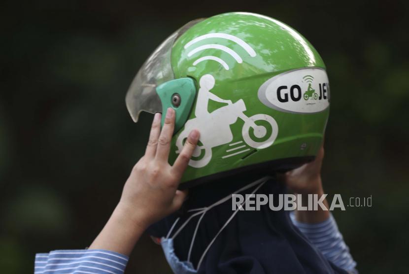 Seorang wanita memegang helm Gojek setelah tiba di sebuah stasiun di Jakarta, Indonesia, Senin, 17 Mei 2021. Perusahaan tumpangan Indonesia Gojek dan perusahaan e-commerce Tokopedia mengatakan pada hari Senin bahwa mereka akan bergabung, dalam kesepakatan terbesar yang pernah ada dalam sejarah negara itu.