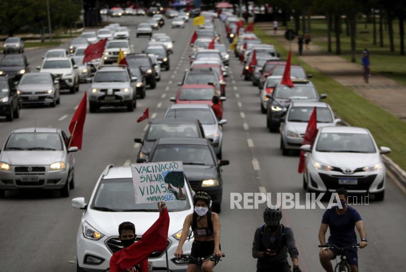 Seorang demonstran membawa poster bertuliskan dalam bahasa Portugis bertuliskan Vaksinasi Menyelamatkan Nyawa di dalam karavan sebagai protes terhadap tanggapan pemerintah dalam memerangi COVID-19 dan menuntut pemakzulan Presiden Brasil Jair Bolsonaro, di Brasilia, Brasil, Sabtu, 21 Februari, 2021.