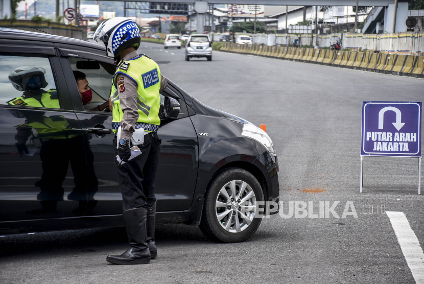 Petugas kepolisian mengarahkan kendaraan untuk memutar balik di Gerbang Keluar Tol Cileunyi, Kabupaten Bandung, Sabtu (23/5). Penindakan berupa pemeriksaan identitas, surat jalan hingga mengarahkan kendaraan untuk memutar balik tersebut ditujukan untuk penyekatan pemudik yang akan menuju jalur selatan dan jalur tengah guna memutus mata rantai penyebaran Covid-19