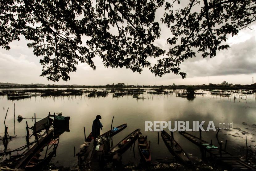 Seorang warga melihat perahu nelayan yang ditambatkan di kawasan waduk di Lhokseumawe, Aceh.