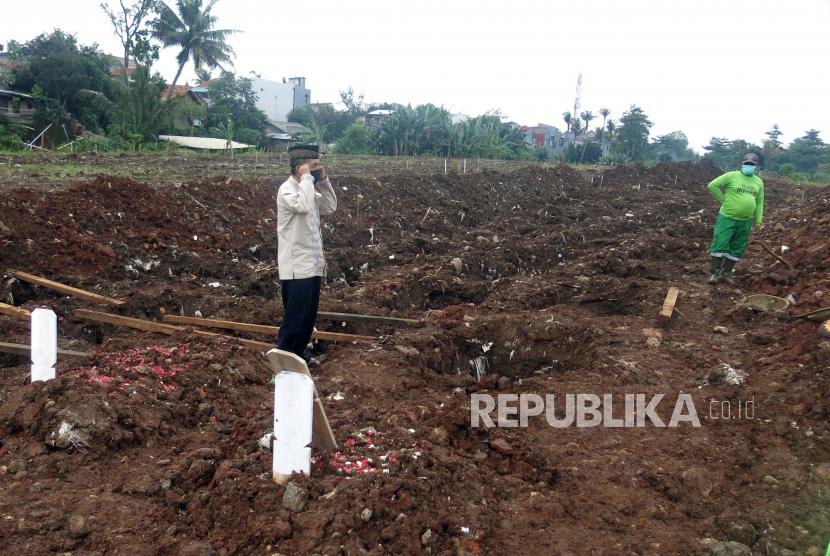 Pihak keluarga korban mengumandangkan azan setelah penguburan jenazah korban Covid-19 di TPU Srengseng Sawah Dua, Jagakarsa, Jakarta Selatan, beberapa waktu lalu.