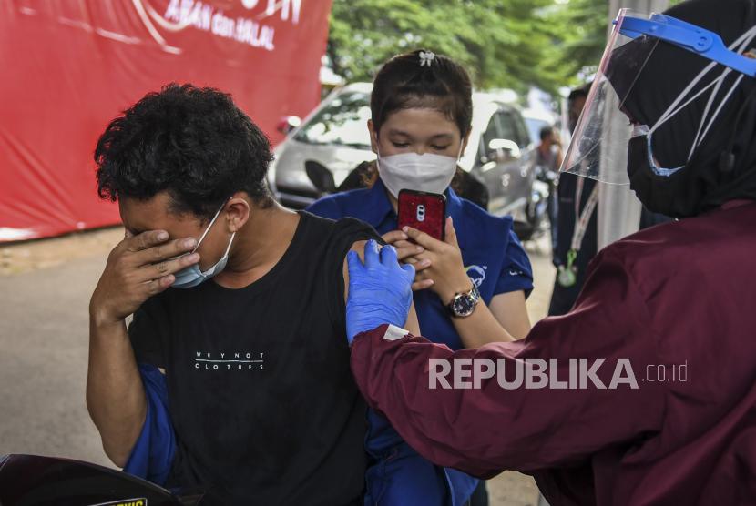 Tenaga kesehatan menyuntikkan vaksin Covid-19 kepada warga secara drive thru di Jakarta Selatan.