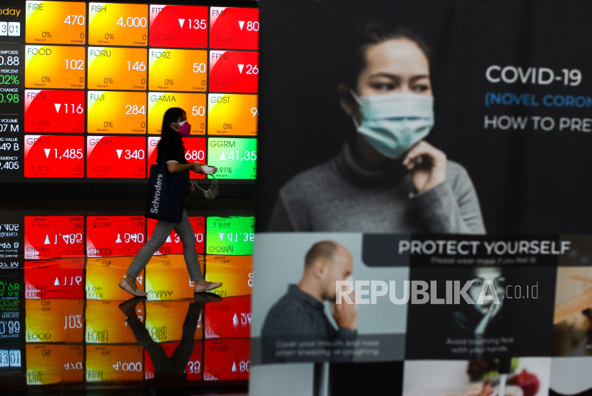 Karyawan melintas di dekat layar pergerakan saham di Bursa Efek Indonesia, Jakarta, Jumat (9/7/2021).