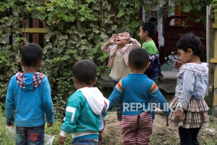 Anak-anak Uighur bermain di luar ruangan di Hotan, Xinjiang, China. (AP Photo/Ng Han Guan)