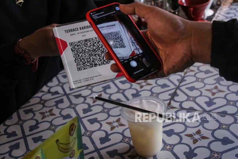 Pembali melakukan transaksi pembayaran digital menggunakan Quick Response Code Indonesian Standard (QRIS) di kedai kopi Terrace Kariraman, Palangkaraya, Kalimantan Tengah, Kamis (1/7/2021). Masyarakat diserukan untuk mengutamakan transaksi non-tunai, termasuk dengan QRIS, untuk mencegah penyebaran Covid-19.