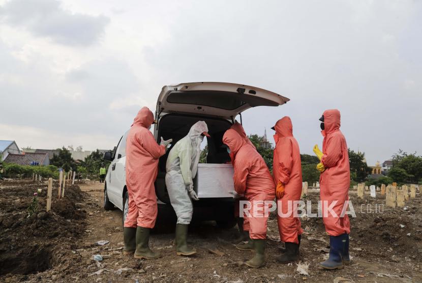 Pekerja yang mengenakan jas hazmat menurunkan peti mati berisi jenazah korban Covid-19 sesaat sebelum dimakamkan (ilustrasi)