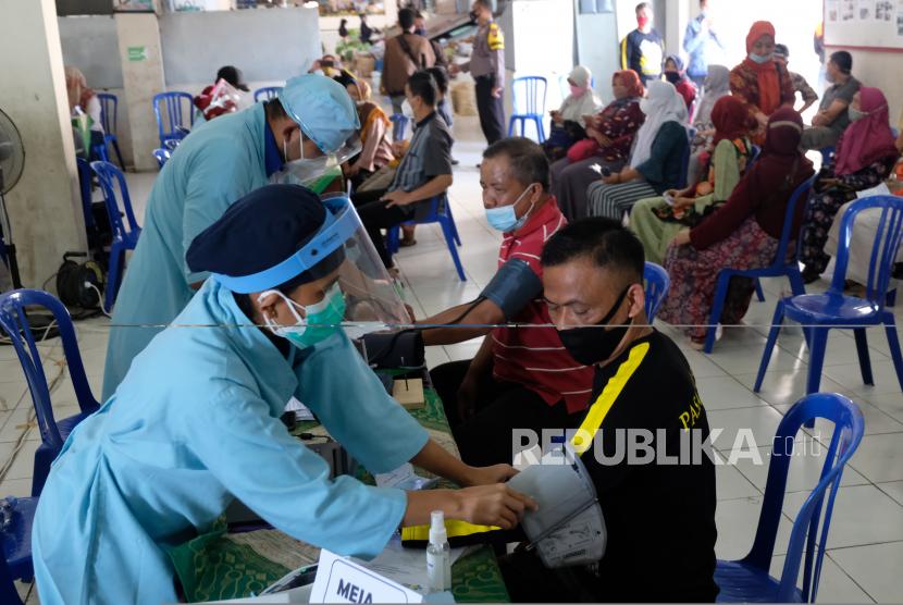 Petugas medis memeriksa kesehatan pedagang saat vaksinasi Covid-19.