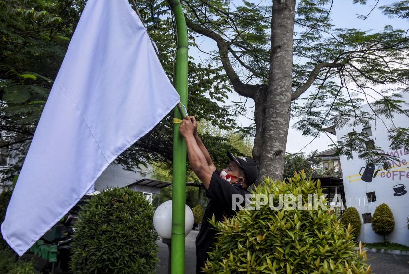 Pekerja memasang bendera putih di salah satu restoran di Jalan Cikutra, Kota Bandung, Kamis (29/7). Sejumlah pengusaha kafe dan restoran di Kota Bandung menggelar aksi pengibaran bendera putih sebagai bentuk protes kebijakan pemerintah yang dinilai tidak mempedulikan nasib para pelaku usaha kafe dan restoran yang terdampak penerapan Pemberlakuan Pembatasan Kegiatan Masyarakat (PPKM). Foto: Republika/Abdan Syakura