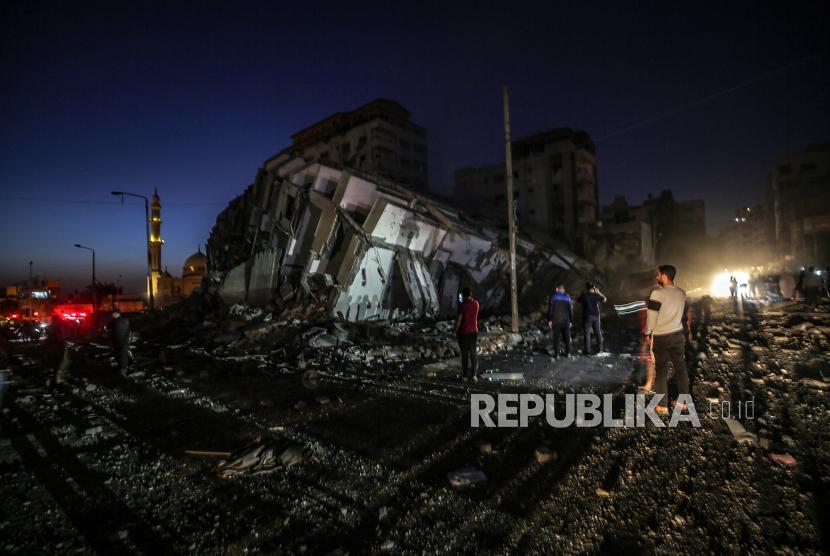 Warga Palestina memeriksa menara Hanadi yang hancur setelah serangan udara Israel di Kota Gaza, 11 Mei 2021.