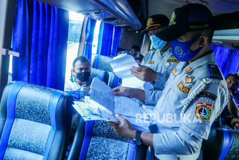 Petugas memeriksa surat izin keluar masuk (SIKM) penumpang di Terminal Kalideres, Jakarta, Jumat (7/5/2021). Terminal Kalideres melakukan penutupan layanan bus AKAP dari tanggal 6-17 Mei 2021 kecuali untuk keperluan mendesak seperti perjalanan dinas, keluarga sakit, dan keluarga meninggal.