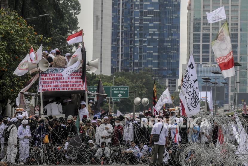 Sejumlah massa saat melaksanakan aksi tolak Rancangan Undang-Undang Haluan Ideologi Pancasila (RUU HIP) di depan Gedung DPR, Senayan, Jakarta, Kamis (16/7). Aksi itu menuntut DPR untuk mencabut RUU HIP dari prolegnas dan pengusutan inisiator RUU tersebut. Republika/Putra M. Akbar