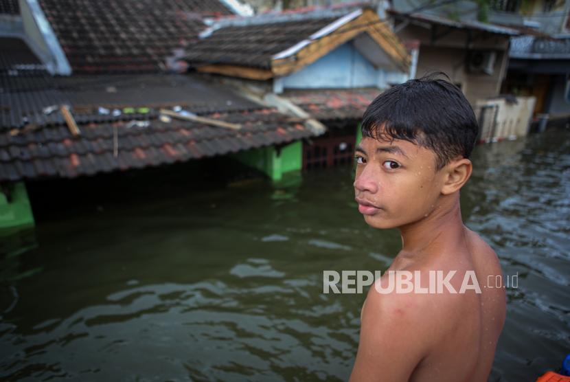 Seorang bocah bermain di kawasan perumahan Periuk Damai yang terendam banjir, Kota Tangerang, Banten, Selasa (23/2/2021). Memasuki hari keempat, kawasan tersebut masih terendam banjir setinggi hingga tiga meter akibat luapan Kali Leduk.