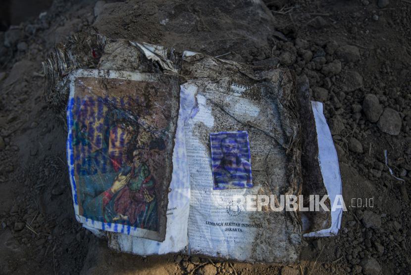 Sebuah kitab suci Alkitab bersama foto pemiliknya berada di antara puing-puing reruntuhan akibat tanah longsor di Desa Waematan, Ile Ape, Kabupaten Lembata, Nusa Tenggara Timur (NTT).